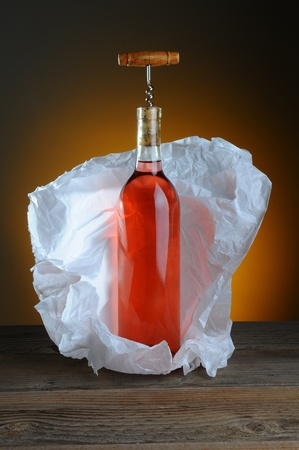 cork screw: A bottle of blush wine wrapped in tissue paper, on a rustic wood surface and a light to dark warm background.A vintage cork screw is inserted in the bottle. Stock Photo