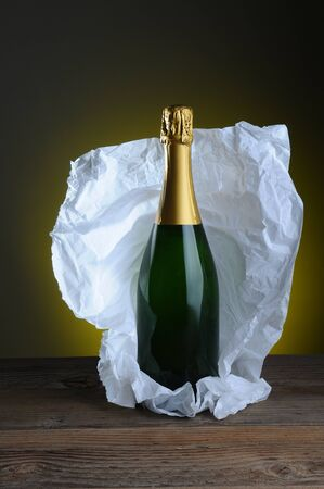 Still life of champagne bottle wrapped in tissue paper on wood surface and light to dark background.