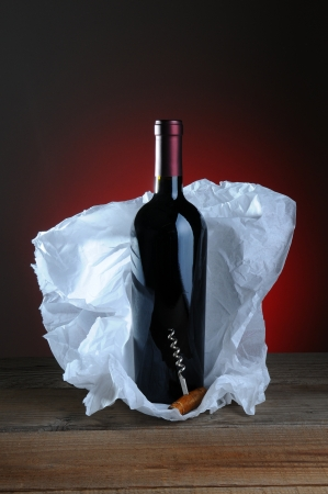 cork screw: Red Wine Bottle and Cork Screw with tissue paper wrapping on wood surface and light to dark background. Stock Photo