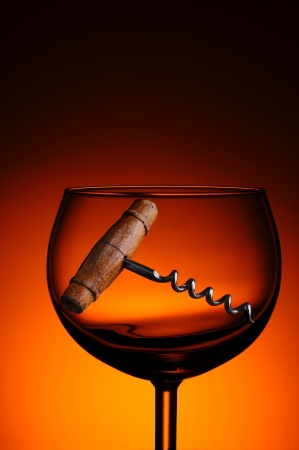 cork screw: An antique cork screw in a wine glass against a warm light to dark background. Stock Photo