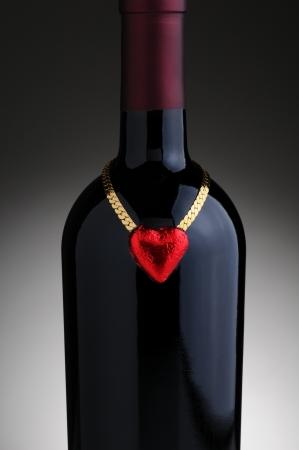 caras emociones: Primer plano de un corazón de chocolate papel de color rojo y la cadena de oro colgando en el cuello de una botella de vino para el Día de San Valentín. Formato vertical en una luz de fondo gris oscuro.