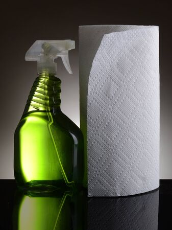 A plastic spray bottle of chemical cleaner and a roll of paper towels on a light to dark gray background  Bottle and towels reflect in the shiny black foreground  Фото со стока