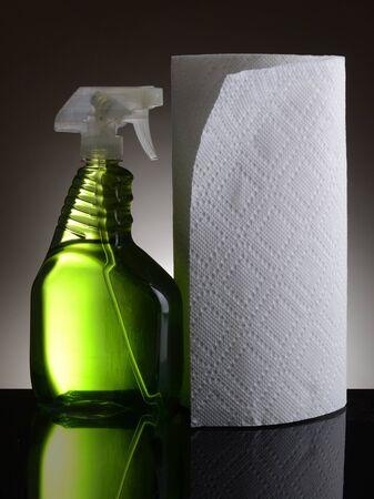 spr�hflasche: Ein Kunststoff-Spr�hflasche der chemischen Reiniger und einer Rolle Papiert�cher auf einer hell-bis dunkelgrau Hintergrund Flasche und Handt�cher spiegeln sich in der gl�nzenden schwarzen Vordergrund Lizenzfreie Bilder