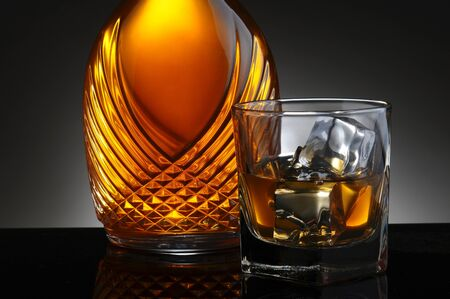 icecube: Closeup of an elegant decanter and a glass of scotch on the rocks  Horizontal format on a light to dark gray background  Stock Photo