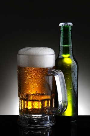 Closeup of a cold mug of beer and bottle on a light to dark gray background Stock Photo - 17786469