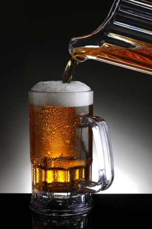 Closeup of a beer mug being filled from a pitcher pouring cold ale into the glass. Vertical format on a light to dark gray background. Stock Photo - 17786495