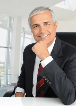 Portrait of a middle aged businessman sitting at his desk with his hand on his chin. Man is smiling at the camera. Vertical format.