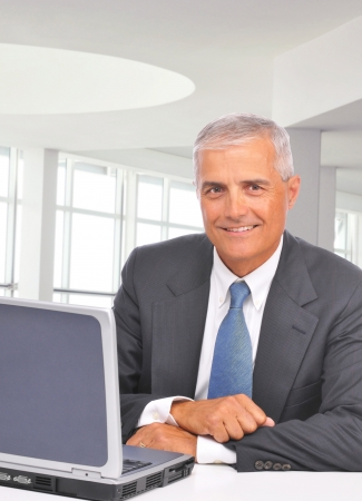 A middle aged businessman sitting at his desk in a modern office with laptop. Man is smiling at the camera. Vertical format.
