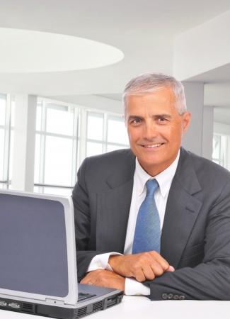 edad media: Un hombre de negocios de mediana edad sentado en su escritorio en una oficina moderna con ordenador port�til. El hombre est� sonriendo a la c�mara. Formato vertical.