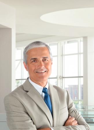 Portrait d'un homme d'affaires d'âge moyen vêtu d'un costume beige clair, les bras croisés dans un environnement de bureau moderne. Format vertical, avec l'homme en souriant. Banque d'images - 17786473