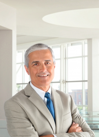 Portrait of a middle aged businessman wearing a light tan suit with his arms folded in a modern office setting. Vertical format, with the man smiling. Stockfoto