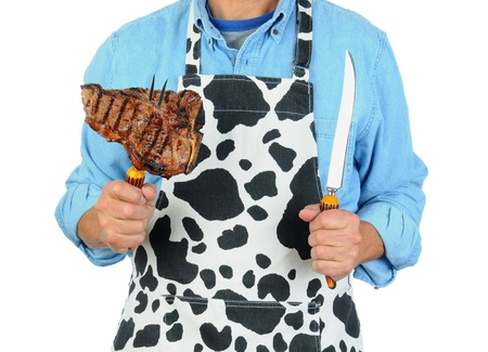 Closeup of a man holding a fork with a barbecued t-bone steak. Man is unrecognizable isolated on a white background. photo
