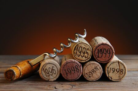 cork screw: Closeup of a group of wine corks and a corkscrew on a rustic wood table and a light to dark warm background.