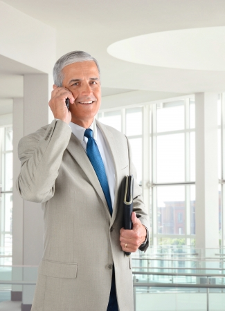 Portrait of a middle aged businessman standing in a modern office talking on a cell phone.. Man is holding a small binder and smiling at the camera. photo
