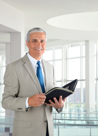 Portrait of a middle aged businessman standing in a modern office. Man is holding a small binder and smiling at the camera.