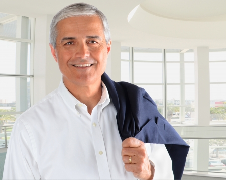 older men: Portrait of a casually dressed businessman in a modern office building. Man is smiling holding his jacket over his shoulder.