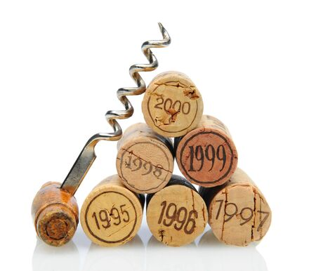 cork screw: Closeup of a group of vintage dated wine corks and an antique corkscrew on white with reflection.