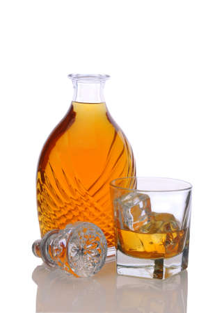 BARWARE: Fancy decanter and a glass of scotch on white with reflection.