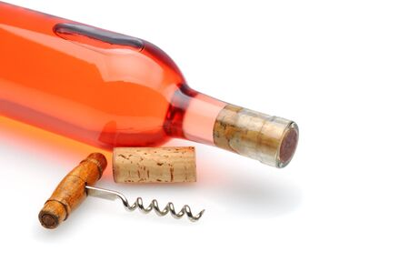 white zinfandel: Closeup of a blush wine bottle and corkscrew laying on a white background with reflection and shadow.  Stock Photo