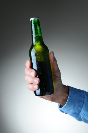 Closeup of a mans hand holding a green beer bottle over a light to dark gray background. Vertical format. Bottle has no label and is covered with condensation. photo