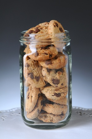 Closeup of a glass jar full of chocolate chip cookies. Vertical format on a light to dark gray background. photo