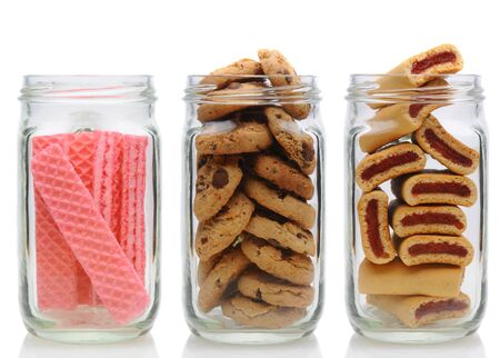 Three glass jars filled with cookies, on a white background with reflection. Jars contain, pink sugar wafers, chocolate chip and fruit bars. photo