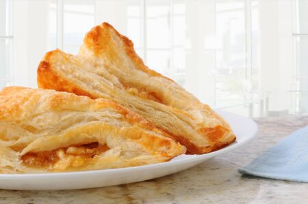 Closeup of two apple turnovers on a plate and granite counter top in a modern diner. Horizontal format background is out of focus and high key. Stockfoto