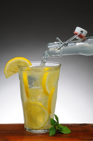 Lemonade pouring into a glass from a bottle. Glass is on a rustic wooden table with a light to dark gray background. photo
