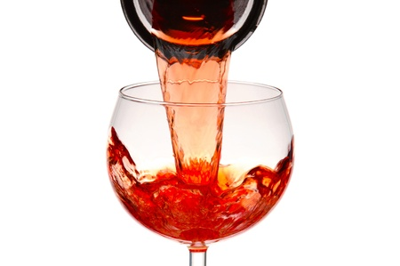 carafe: Closeup of a wineglass with red wine pouring from a carafe. Stock Photo