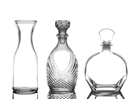 depicted: Closeup of three glass decanters on white with reflections. Wine Carafe and cognac decanters are depicted. Stock Photo