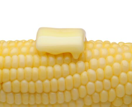 shucked: Closeup of an ear of corn with a pat of melting butter. Horizontal format on white.