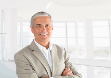 Closeup of a casual businessman in a modern office with his arms folded. Horizontal Format. Stockfoto