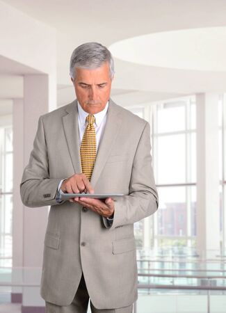 Middle aged businessman looking at his tablet computer while standing in a modern office building. photo