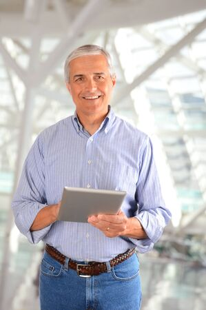 Closeup of a casual businessman in a modern factory holding a tablet computer. Vertical Format. Stockfoto
