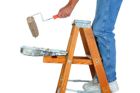 Closeup of a painter standing on a ladder with a roller dripping paint. Man is unrecognizable on a white background. Stock Photo - 18589820