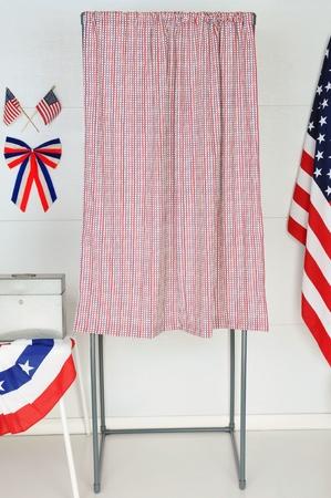 encuestando: Una cabina de votación individual con banderas de Estados Unidos y gallardetes con una mesa y urna.