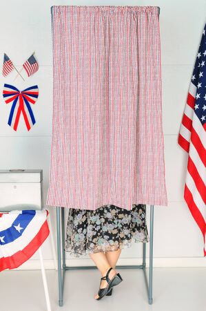 encuestando: Un votante mujer en el interior de una cabina de votaci�n en su lugar de votaci�n local. Foto de archivo