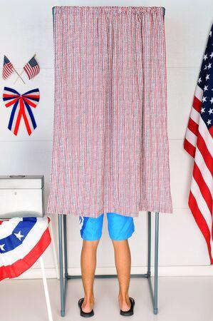 encuestando: Un votante masculino joven en el interior de una cabina de votación en su lugar de votación local.