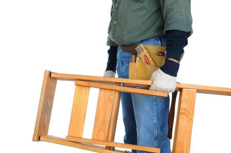 Closeup of a construction worker carrying a wooden ladder in his hand.  Horizontal format on a white background. Man is unrecognizable. photo