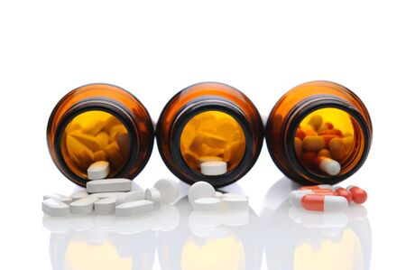 Closeup of three brown prescription bottles on their sides with pills spilling onto white reflective surface. Shallow depth of field with focus on foreground medicine.
