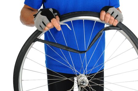 pry: Closeup of a cyclist repairing a flat tire. Tube is hanging part way out of the tire as the man stands behind in cycling clothes over a white background. Stock Photo