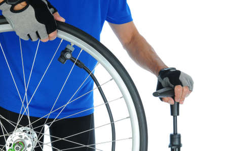 pumping: Closeup of a cyclist pumping up a bicycle tire. Man is unrecognizable and standing behind the wheel. Horizontal format over a white background.