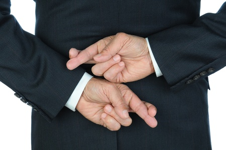 unethical: Closeup of a business man with his hands behind his back and fingers crossed. Torso and hands only, man is unrecognizable. Stock Photo