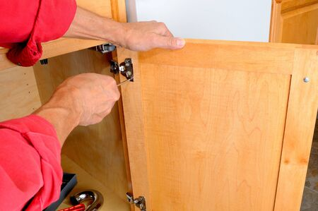 Home repair: Closeup of a installers hands attaching a hinge a kitchen cabinet.