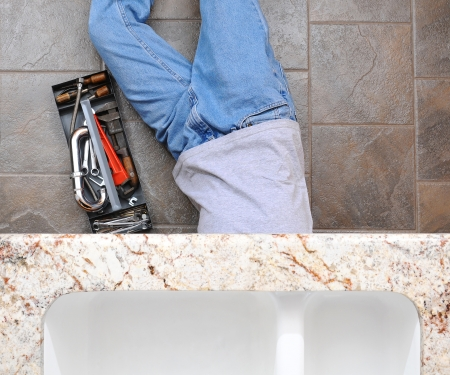 pipe wrench: High angle view of a plumber laying under a kitchen sink. Man is unrecognizable with a tool box next to him.