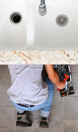 High angle view of a plumber under a kitchen sink reaching for a wrench from the tool box next to him. Man is unrecognizable. Vertical Format.