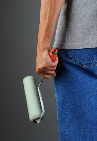 Closeup of a male painter seen from behind while he holds a paint roller by his side. Man is unrecognizable, torso and legs only. Vertical format. Stock Photo - 18871414