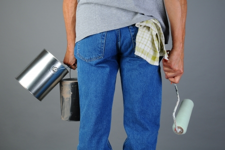 Closeup of a male painter seen from behind while he carries two paint cans and a roller. Man is unrecognizable, torso and legs only. Horizontal format. Stock Photo - 18871410