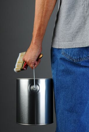 Closeup of a male painter seen from behind while he carries a paint can and brush. Man is unrecognizable, torso and legs only. Vertical format. Stock Photo - 18871412