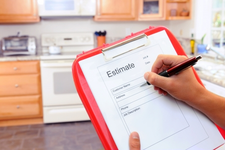 Closeup of a contractors clipboard as he writes up an estimate for a kitchen remodel. Shallow depth of field with focus on clipboard. Imagens